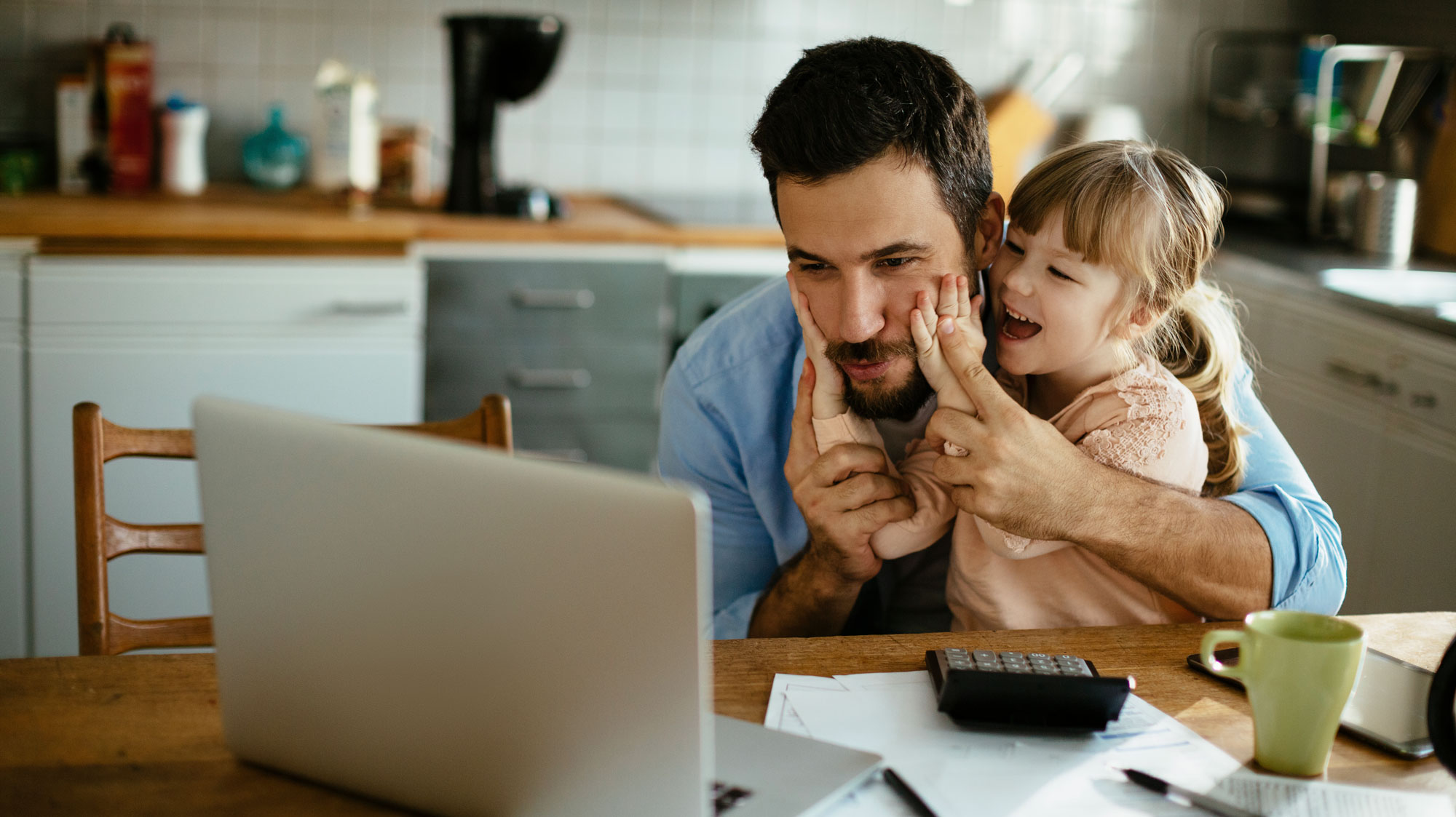 Father sitting looking at computer with daughter on lap squishing his cheeks