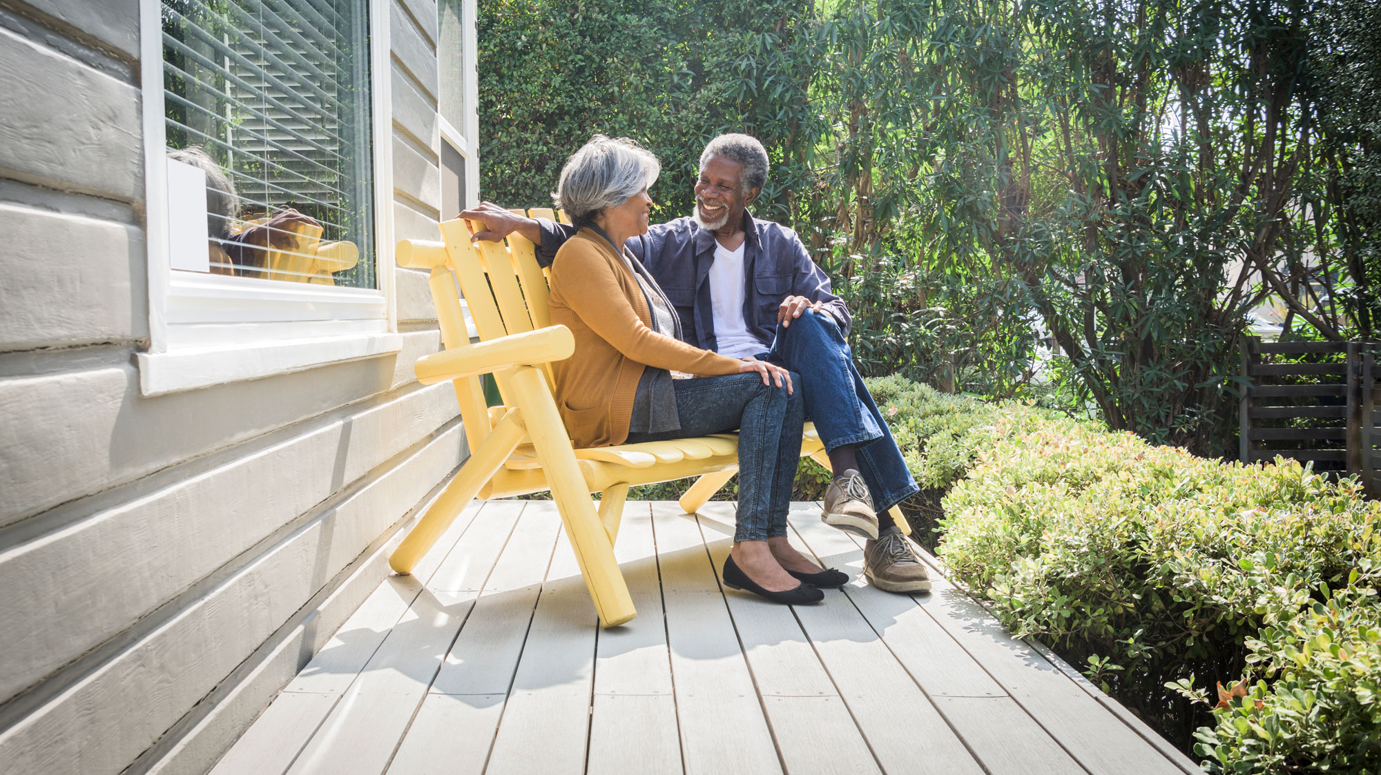 Elderly couple sitting on bench on a porch