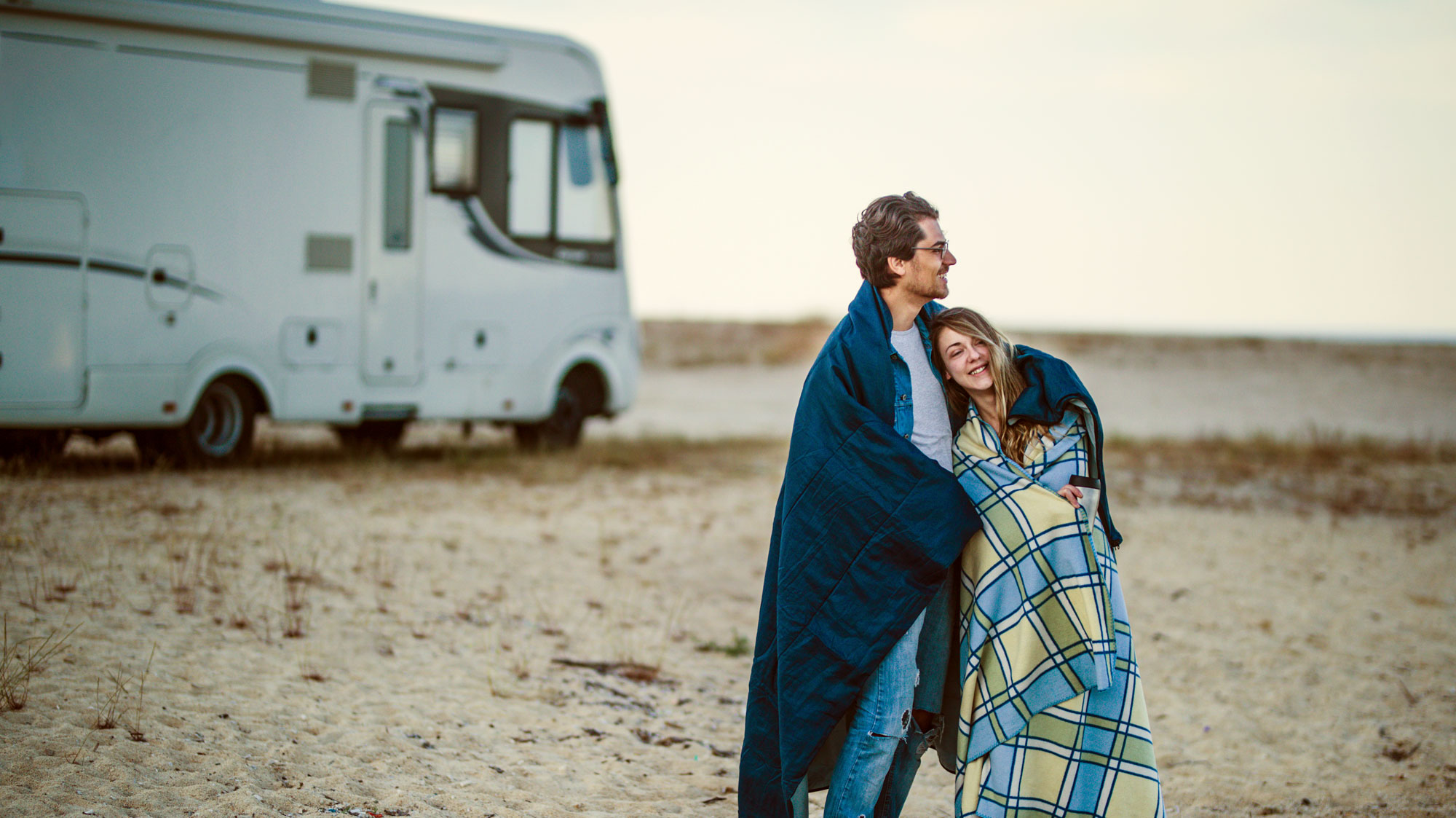 man and woman wrapped in blankets with RV in background