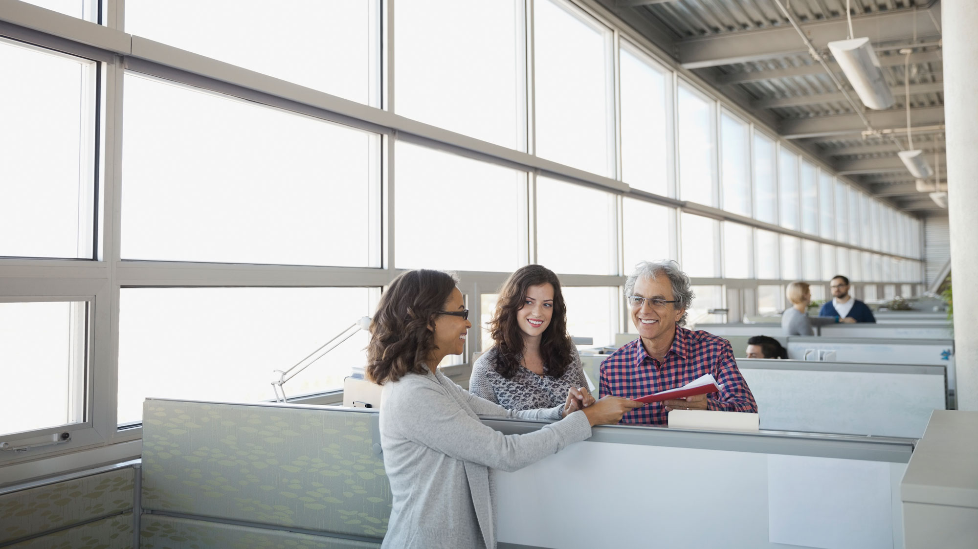Two women and a man in a cubical exchanging a folder over the cubical wall