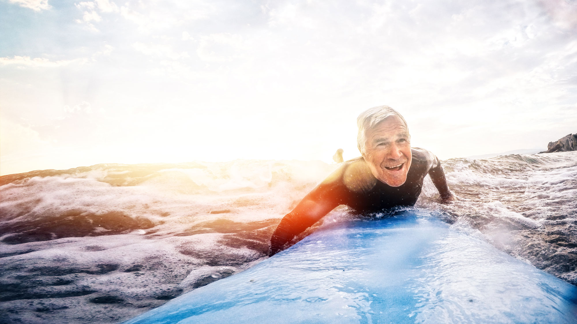 Older man smiling and surfing