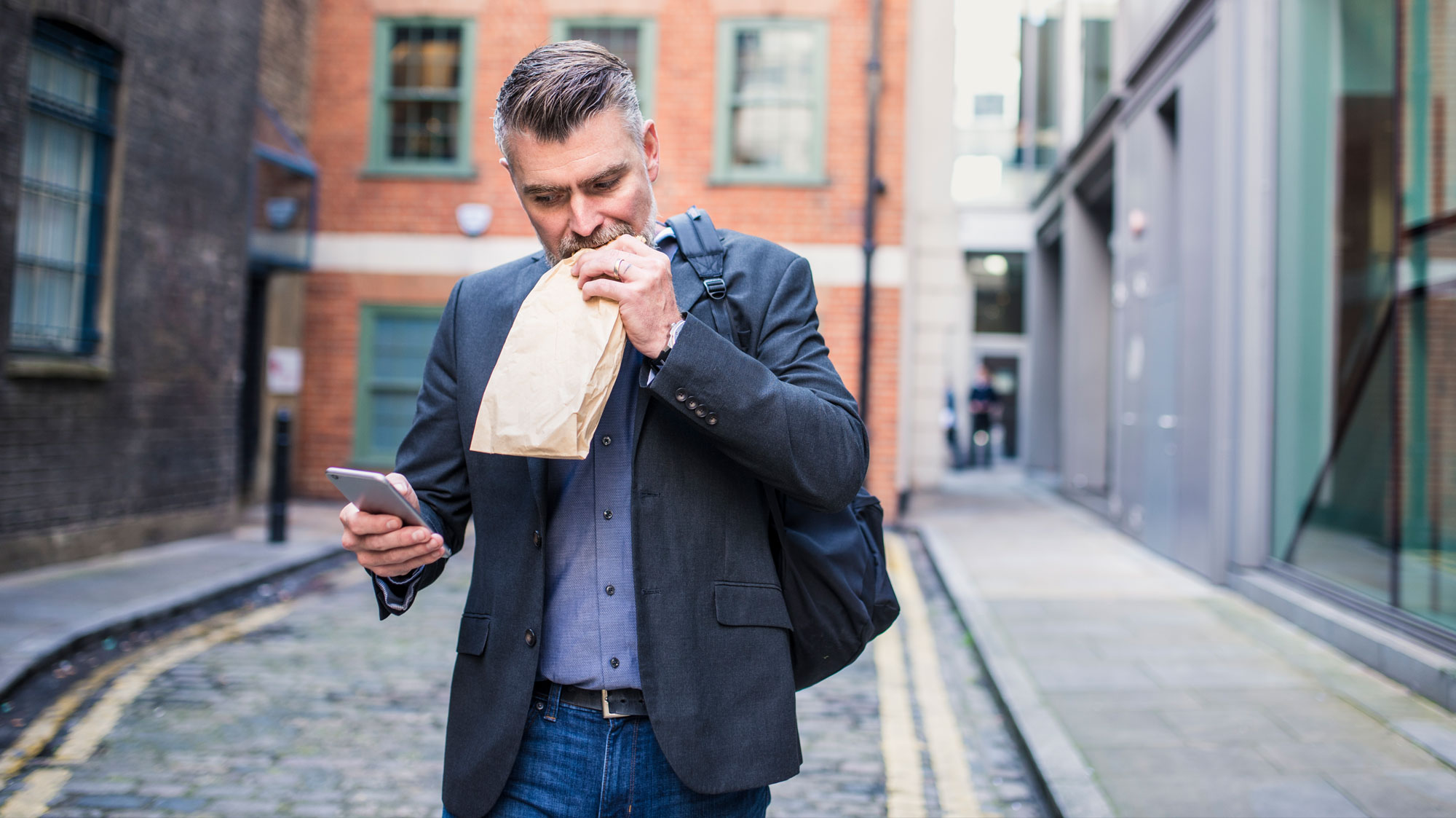 Man walking, eating and looking at his phone