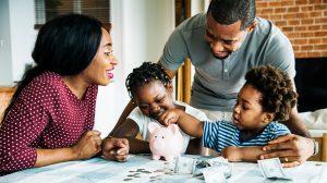 Children saving money in piggy bank, parents smiling