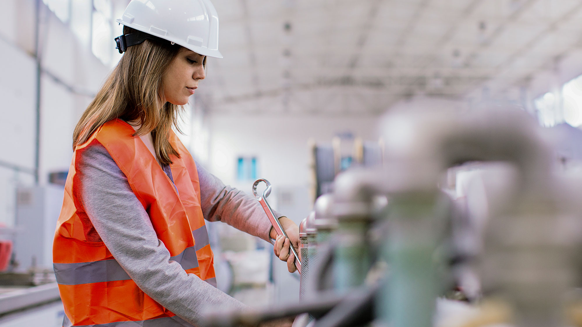 Woman in a hard hat and safety vest on a manufacturing line