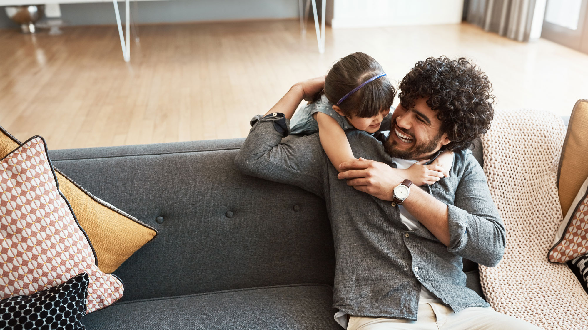 Young daughter smiling and hugging dad who is sitting on a couch