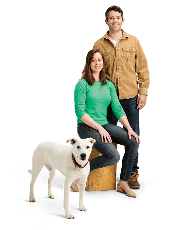 Woman sitting on stump, Man and dog standing