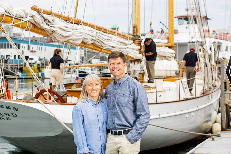 Portland Schooner Company owners in front of sailboat