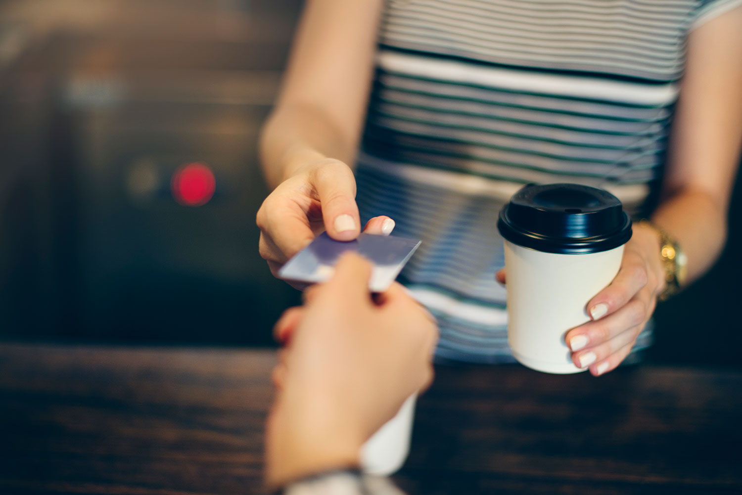 Photo of person buying coffee with debit card