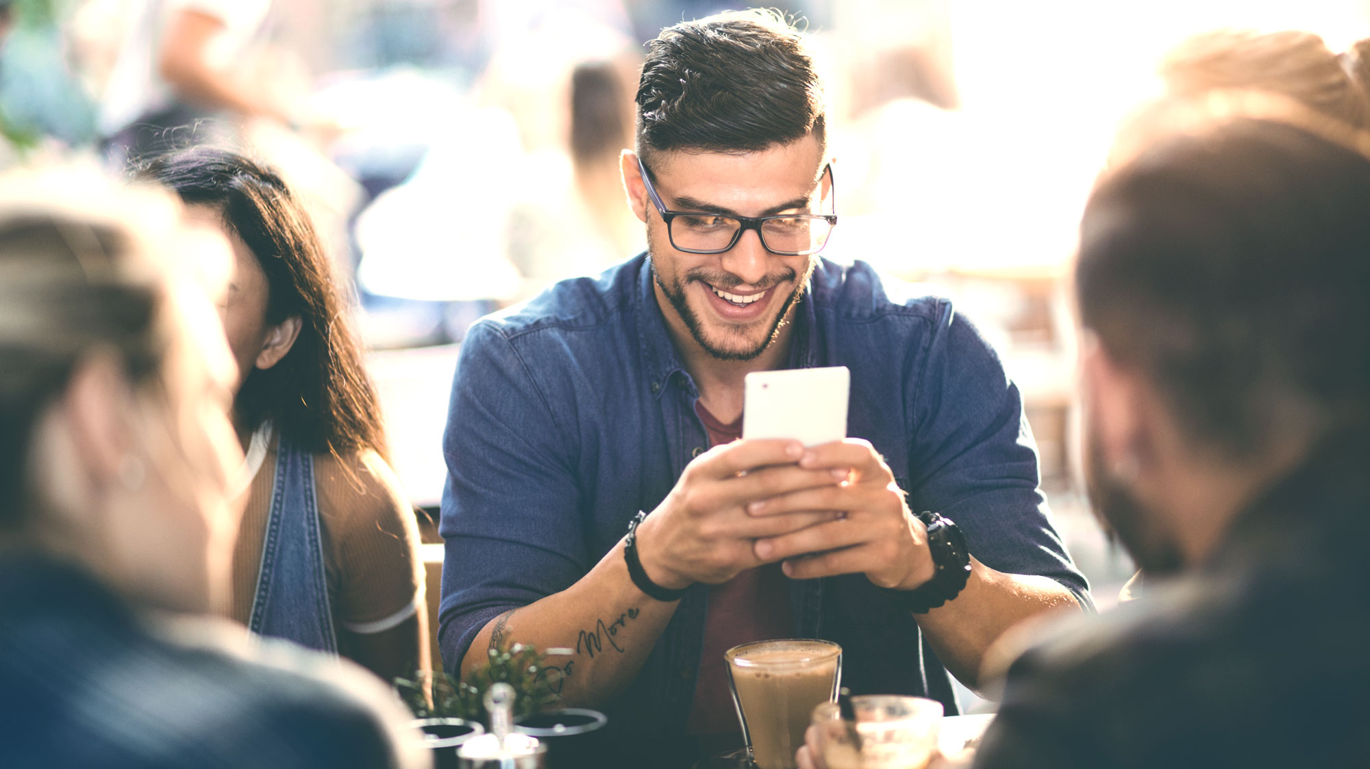 Man using Zelle on Smartphone sitting with friends